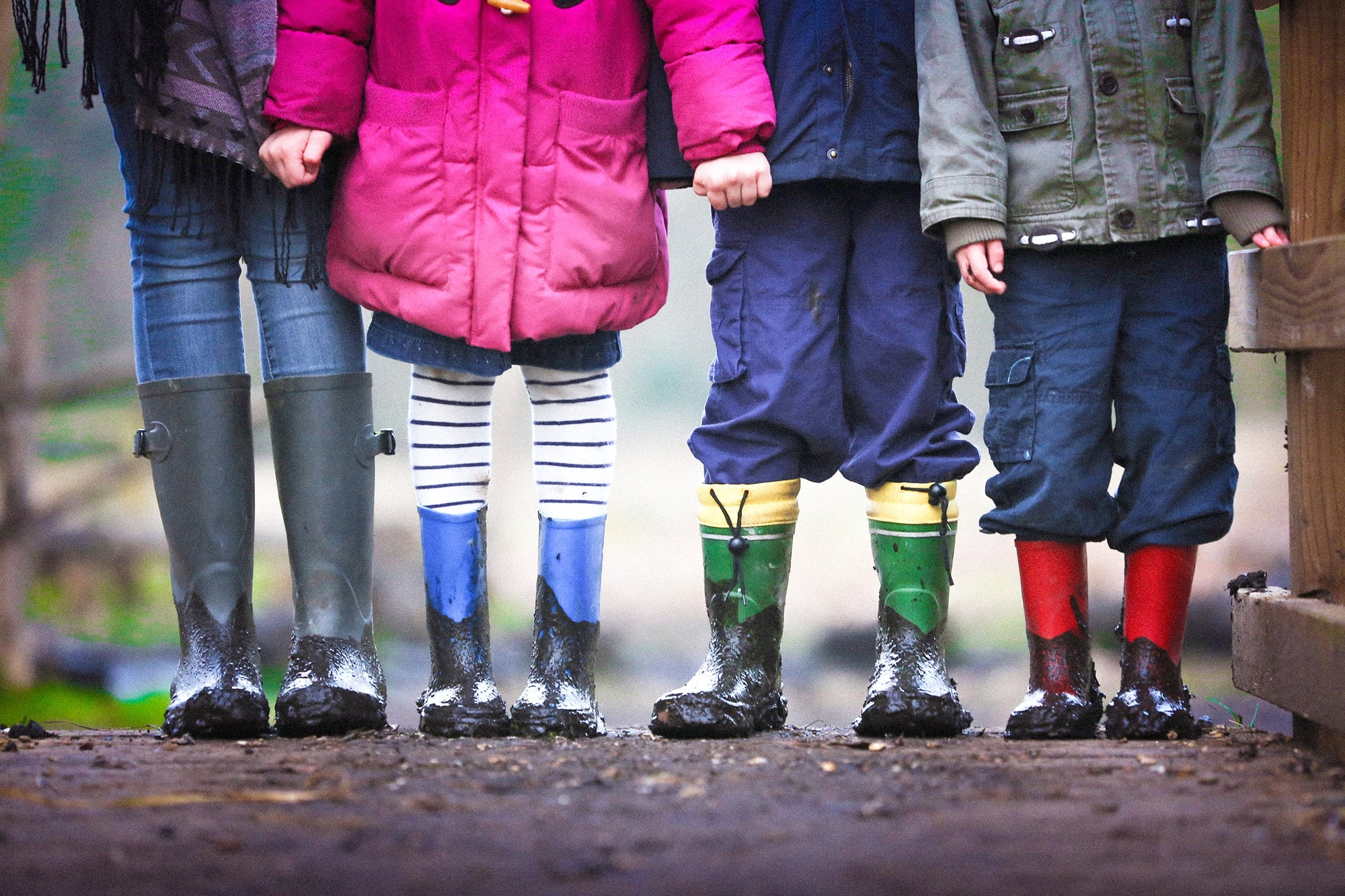 Vier Kinder mit bunten, schmutzigen Regenstiefeln
